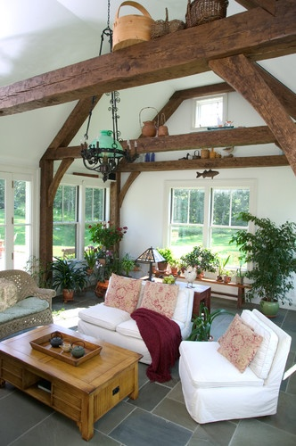 Plant filled sun room with stone floor and rustic posts and beams - frankshirleyarchitects.com