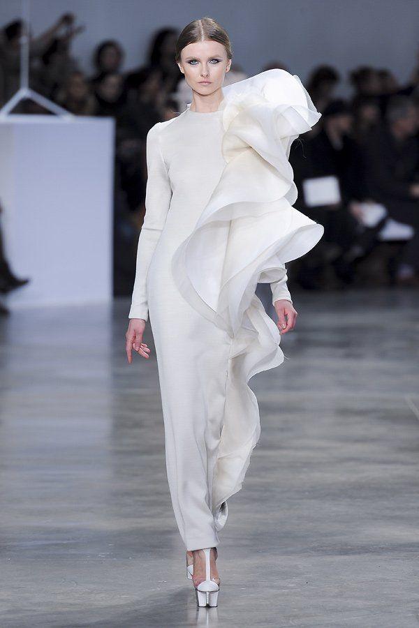 Kühler Minimalismus trifft Romantik: Die übergroßen Volants sorgen für einen dramatischen Auftritt, bei Stéphane Rolland Haute Couture 2013.Was sind Volants? Rund geschnittene Stoffstreifen unterschiedlicher Breite werden ohne Einkräuselung an Ärmeln, Saumkanten, Ausschnitten etc. angesetzt. Durch die Schnittform fällt der Volant glockig. Er steht für einen femininen romantischen Stil.Was versteht man unter Jabot? Dekoration aus Rüschen oder Volants, meist aus feinem Stoff, die Blusen und…
