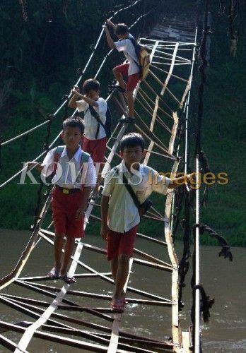 Siswa SDN Cigoong 2 berangkat sekolah dengan meniti jembatan rusak yang menghubungkan Desa Karyajaya dan Desa Cigoong Selatan, Lebak, Banten, Senin (7/4/2014). Sudah dua tahun para murid melintasi jembatan ini untuk menuju sekolah, karena jika memutar mereka harus menempuh jarak sejauh tiga kilometer.