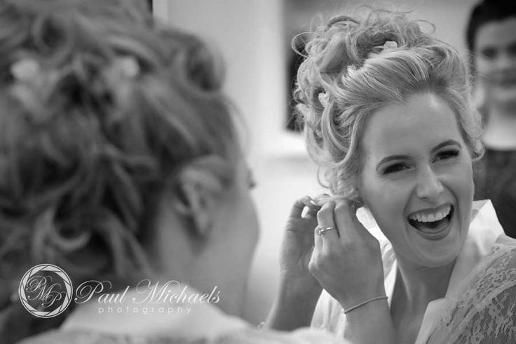 Emma puts on her earings in the mirror. Wellington wedding photography http://www.paulmichaels.co.nz/