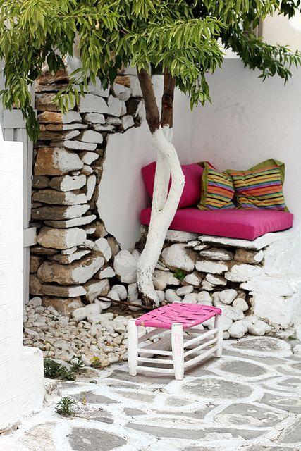 white walls, stone floor, plants, cushions