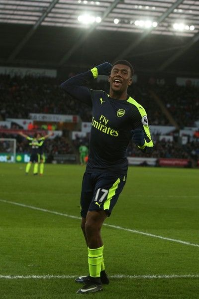 Arsenal's Nigerian striker Alex Iwobi celebrates his team's second goal after his shot was defelected into goal off Swansea City's English midfielder Jack Cork (unseen) during the English Premier League football match between Swansea City and Arsenal at The Liberty Stadium in Swansea, south Wales on January 14, 2017. / AFP / Geoff CADDICK / RESTRICTED TO EDITORIAL USE. No use with unauthorized audio, video, data, fixture lists, club/league logos or 'live' services. Online in-match use…