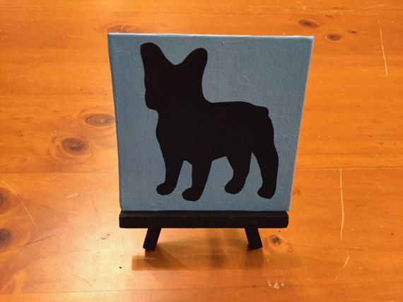 French Bulldog Mini Easel Canvas  4x4in canvas  blue background/ black design  Includes black wooden easel (the canvas is not glued to it)  Handmade  Perfect for your desk  Custom canvases are available on request  If you have any questions, please feel free to ask
