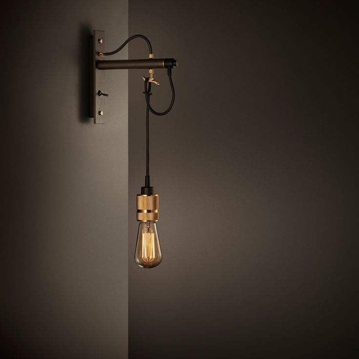 A wall light made from bronzed gun metal and finished with knurled brass and matte rubber detailing. The body houses a brass customising hook to allow the lig