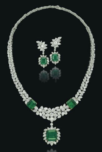 A SET OF EMERALD AND DIAMOND JEWELLERY Comprising a necklace designed as a flexible band of brilliant-cut, marquise and pear-shaped diamonds, enhanced with two square-cut emeralds at the front and suspending a detachable pendant, and a pair of ear pendants en suite, the back of the necklace can detach to be worn as a bracelet, mounted in platinum and gold. (Christie's)