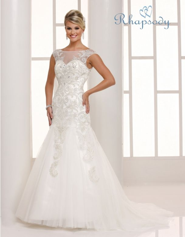 Rhapsody  Style #R7702  An alluring bridal creation for today! There is a sweetheart neckline and a sheer yolk. This dress has a sheath torso with beautiful and unique embroidery on soft net over rich duchess satin and a trumpet skirt of tulle. There is a chapel train.