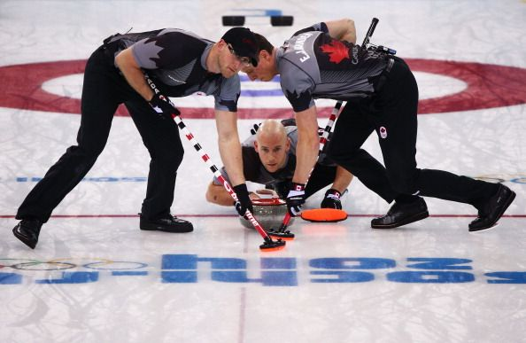 Ryan Fry of Canada (C) plays a stone as Ryan Harnden (L) and EJ Harnden (R) assist during the Men's Gold Medal match between Canada and Great Britain (c) Getty Images