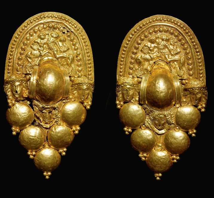 Etruscan gold earrings, late 4th-early 3rd century B.C. A grappolo type, each with upper horseshoe-shaped plaque repousse in relief with a centaur fighting a helmeted and curaissed warrior within two borders of applied bosses, the central crescentic  element  flanked by the heads of two wreathed goddesses above a central mask of a deity with backward-streaming hair, five lentoid beads, a rosette, 11.7 cm high. Private collection