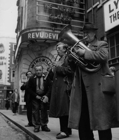 Robert Doisneau | Musiciens de rue, Londres 1956 Street musicians in Soho London, outside The Windmill Theatre, Great Windmill Street.
