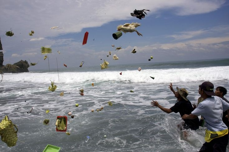 Indonesian men try to catch offerings thrown into the sea by Hindu worshipers during the ritual of Melasti on a beach in Gunung Kidul, Yogyakarta. The ritual which is performed ahead of Balinese Hindu's Day of Silence, is held to purify the universe from bad influences, bad deeds and bad thoughts.