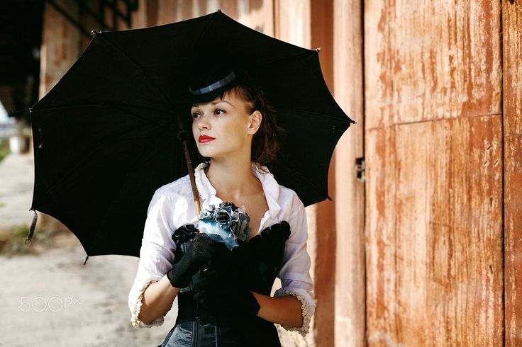 Woman in Historical Costume - Portrait of Sexy Beautiful Woman in Historical Costume with Black Umbrella. Female Standing on the Abandoned Railway Station. Book Cover Concept.
