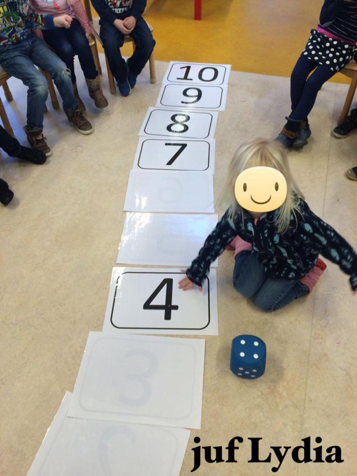We leggen samen de spring/getallenmatten op goede volgorde in de grote kring. Daarna de dobbelsteen rollen en wat gegooid is omkeren. We komen er al gauw achter dat we twee dobbelstenen nodig hebben om alle getallen te kunnen omdraaien. We oefenen daarna in groepjes met kleine getallenkaartjes en dobbelstenen. Er kan daarna tijdens de werkles nog eens worden geoefend/verwerkt.