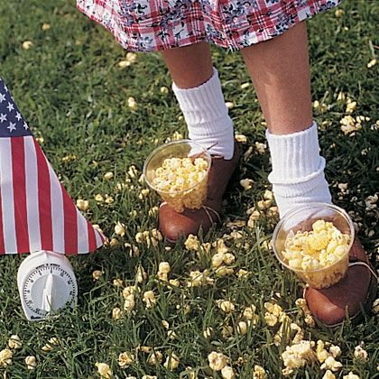 Popcorn Relay Race.  Strap cups of popcorn onto feet and race to fill up a box/bucket.