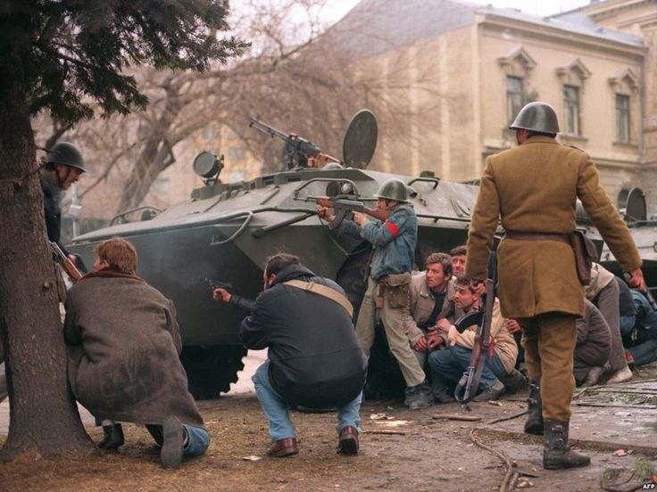 Romanian civilians and soldiers in cover behind a armored vehicle fighting…