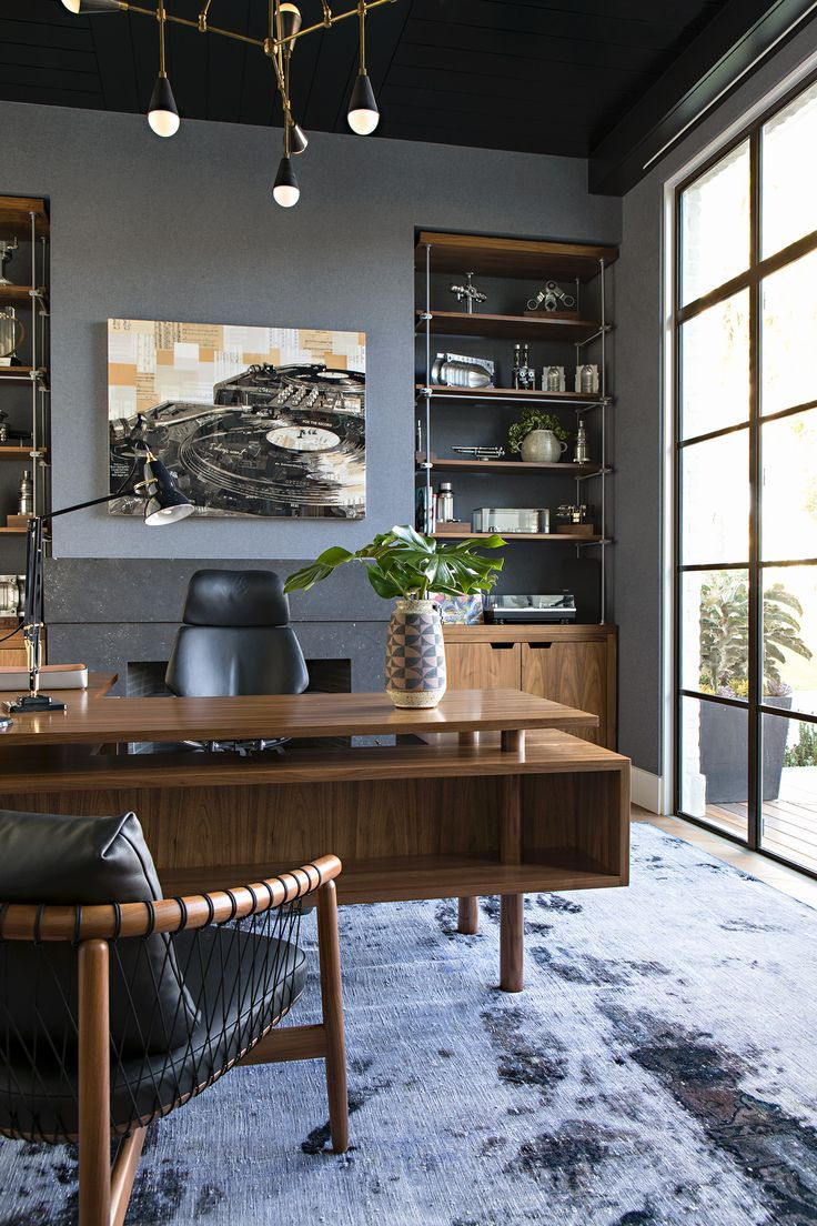 The owner's home office has custom brass and walnut built-ins that house a collection of machine parts. The walls are upholstered in grayish blue flannel, while Heidi Bonesteel designed the midcentury desk with a return that has shallow bookshelves in front. The chandelier is Apparatus, and the armchair is from Design Within Reach. Masculine office