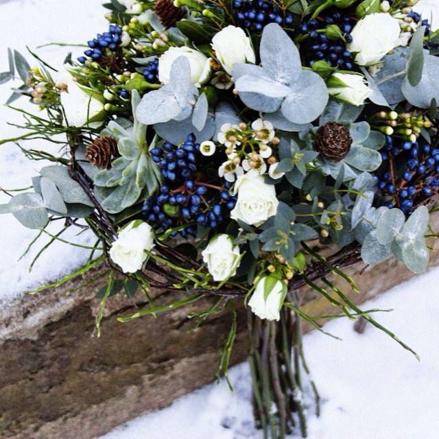 En jordnära brudbukett med kvistrosor, viburnum, eucalyptus, blåbärsris, vaxblomma.