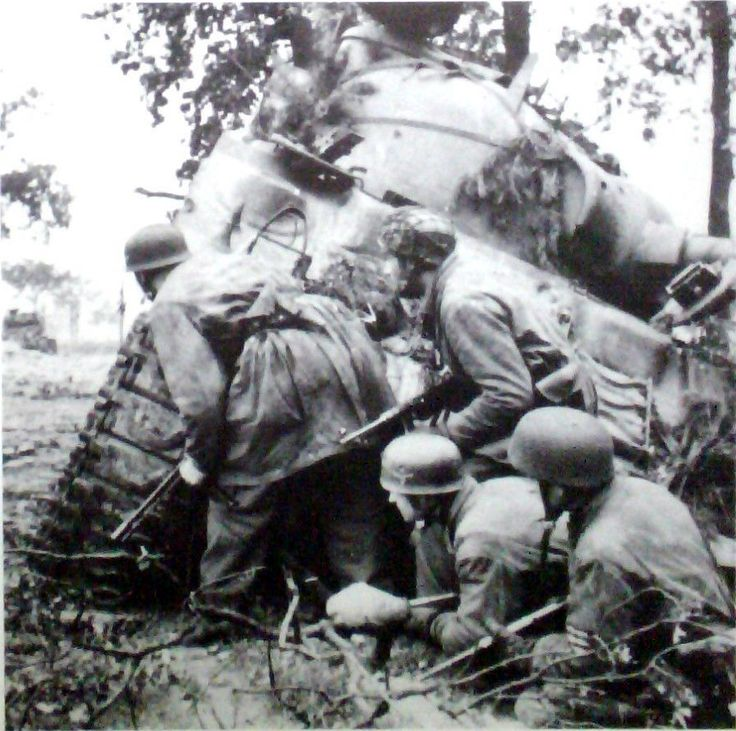 German paratroopers, Fallschirmjäger, take shelter next to a knocked out M4 Sherman while cautiously peering for another target. In the distance a Sherman is stalking them.