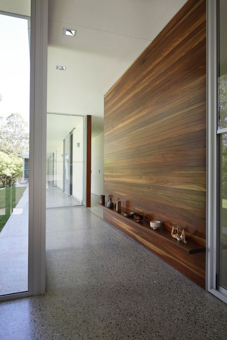 For their family home in Brisbane, Australia, John and Cathy Dillon spent countless hours poring over design magazines and books to strike the right updated-mid-century-modern balance. This spacious outdoor hallway boasts a bottom shelf which provides an attractive space to display the family's pottery collection.