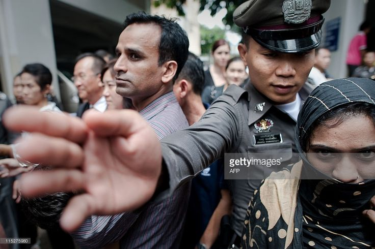 A Thai immigration police officer (C) directs pakistani refugees released on bail to a waiting bus after their detention at the Immigration detention centre in Bangkok on June 6, 2011. A group of almost a hundred pakistani refugees and asylum seekers, including several dozen children and a baby born in detention, were released on bail. AFP PHOTO/ Nicolas ASFOURI (Photo credit should read NICOLAS ASFOURI/AFP/Getty Images)
