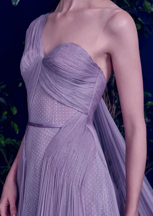 A Lavender Spell  A Lavender Spell is crafted of hand-pleated tulle that drapes across the hips in an asymmetrical design, as well as a pleated shoulder panel that cascades down. It features a pleated bodice, layers of lavender tulle, mixing dotted tulle with sheer lavender layers. •Hidden side zip •Illusion tulle neckline •Decorative semi-belt •Boned corset •Fully lined •Composition: Self: silk tulle; Lining: crepe georgette •Color: lavender •Made in the UAE