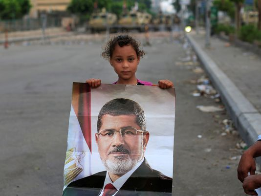 Egypt News Today   supporter of ousted Egypt President Mohammed Morsi poses with his ...