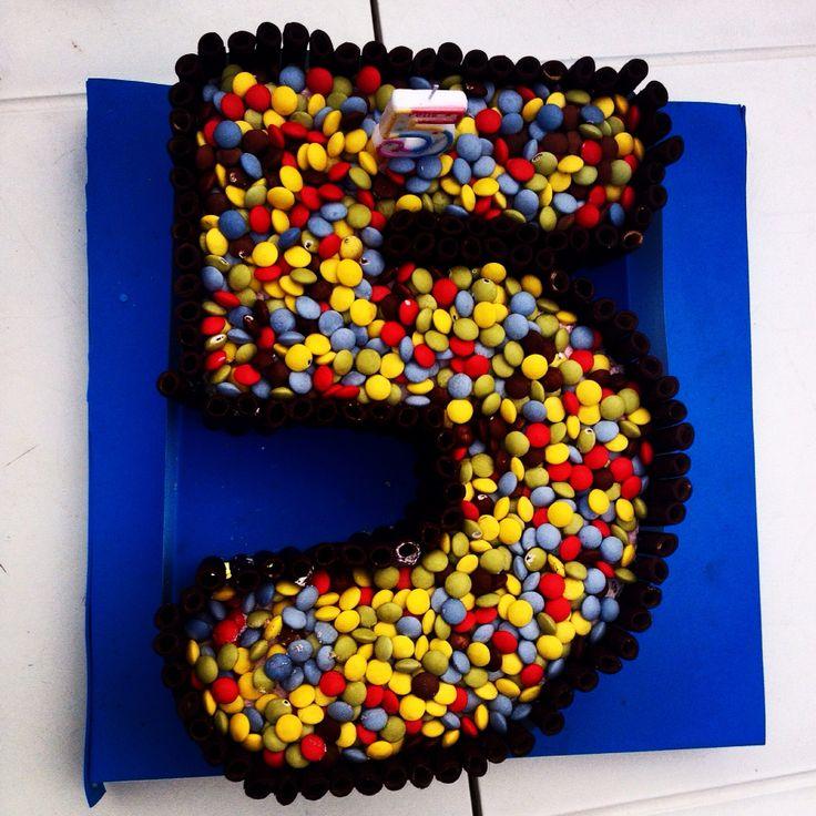 Tarta de cumpleaños del número 5, hecha con mufins y chocolates cubiertos de colores (lacasitos), rellena de bizcocho de vainilla con crema de frutas del bosque, bañada en su almíbar. Está más rica!!!