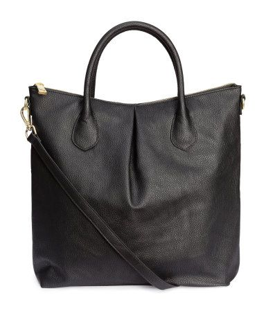 Soft handbag in grained imitation leather. Pleat at front and back, zip and two handles at top, and detachable shoulder strap. Three inner compartments, one with zip. Lined. Size 14 1/4 x 16 1/2 in.
