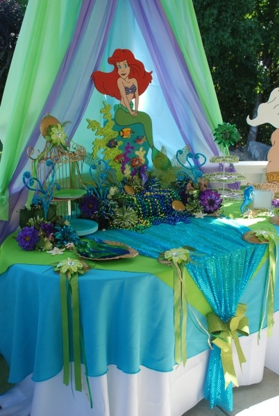 Little Mermaid theme party. Cute table cloth decorations. I also hung fish net and large shells all over the backyard. We had a photo wall I had decorated with tons of sea and items and used apolaroid camera. The kids love it. They all gott hula skirts and leis.