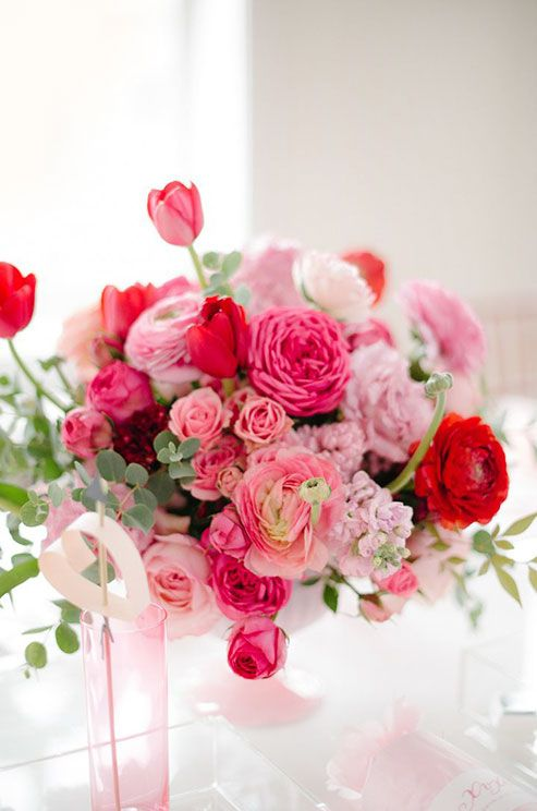 Varying shades of pink add depth to this centerpiece of ranunculus, tulips and pink sweet peas.