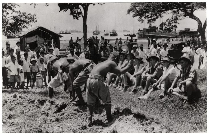 1939-1945. Travail forcé de PG japonais sous le regard des PG australiens libérés. During the Japanese occupation of Malaya, Australian PoWs were made to dig trenches for the defense of Singapore. Now the released Australian PoWs sit and watch Japanese PoWs fill in the selfsame trenches.
