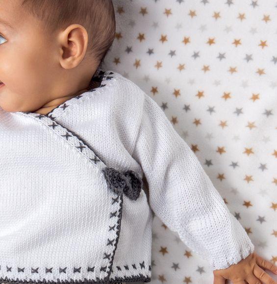 On craque pour ce petit modèle de gilet cache-coeur aux extrémités côtelées et aux couleurs douces. Modèle tricoté en '3.r.htmlstyle=text-decoration:underline;color:#6B7785;>Fil phil coton 3' coloris Blanc et Minerai au point jersey et côtes 2/2. On aime la petite broderie sur tout le contour du gilet et le petit noeud pour fermer le modèle. Modèle n°01 du catalogue N°120 : Enfant et Layette, Printemps / été 2015