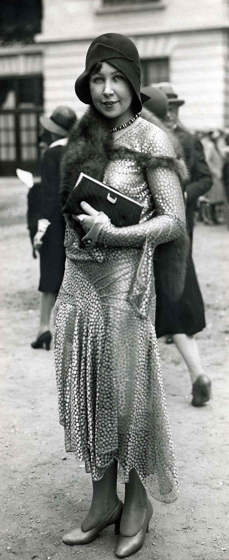 14-11-11  Damesmode. Op de renbaan bij Longchamps wordt de laatste mode getoond. Japon met lage taille en ongelijke rokrand. Om de hals een vosje. Het model draagt daarbij een helmvormige hoed en hoge hakken. Longchamps, Frankrijk, 1929.