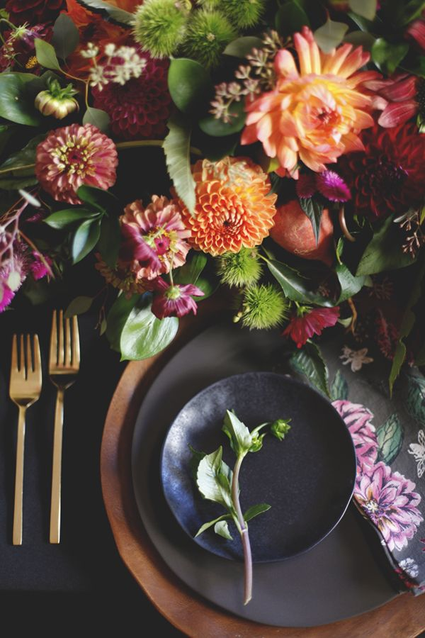 black table setting with deep colored flowers