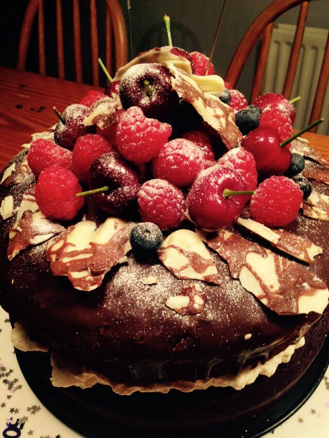 Chocolate cake with fresh cream and topped with chocolate sauce, berries and chocolate flakes