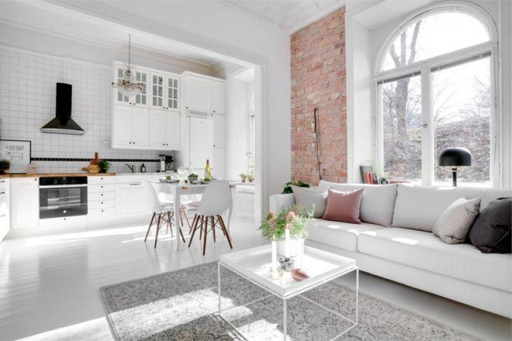 otwarty salon z kuchnią w białej aranzacji z jedną ścianą z czerwonej cegły - Lovingit.pl