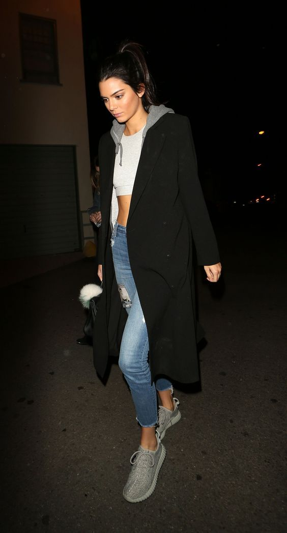 Kendall Jenner: cropped top off-white + hoodie cinza + casaco preto + jeans + Adidas Yeezus #fashion