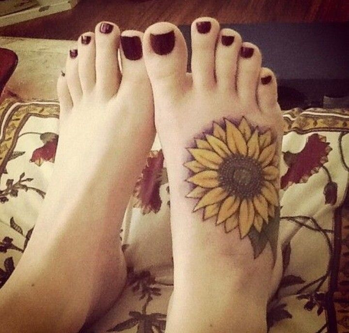 Colored sunflower foot tattoo with leaves.