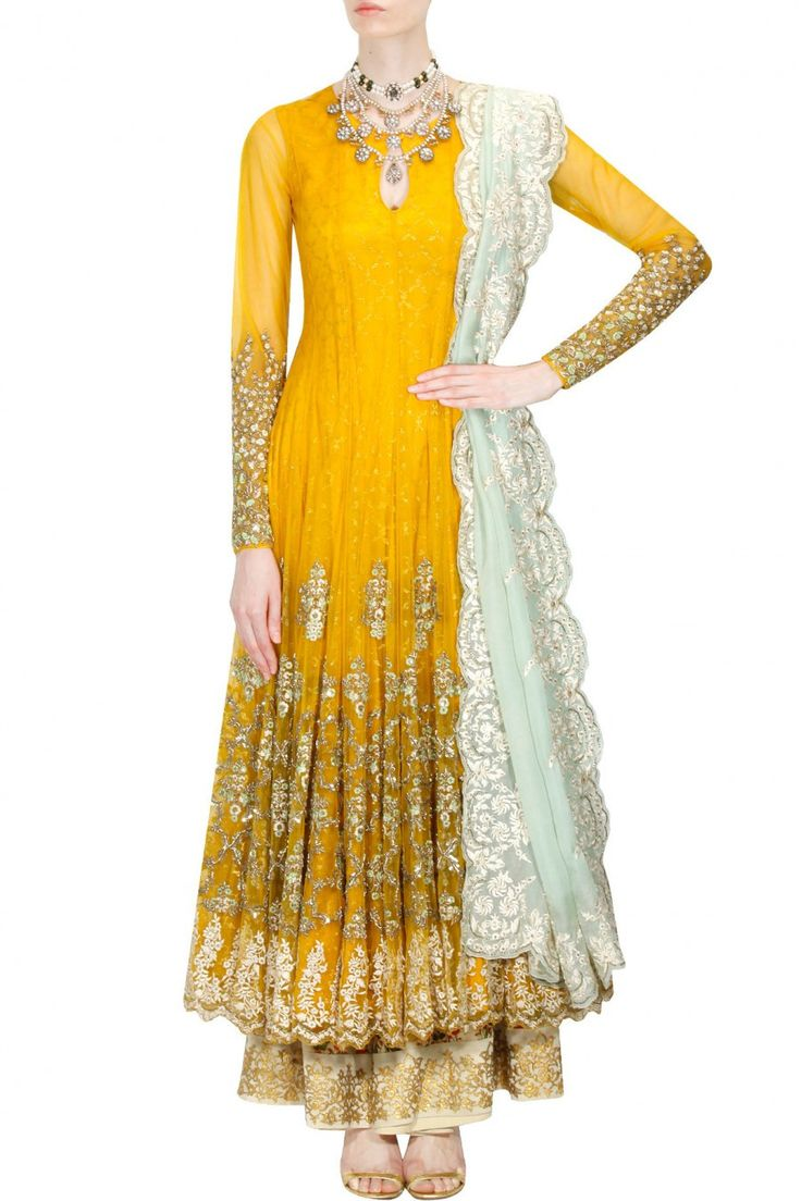This set features a mustard yellow anarkali kurta in net base with white and mint green floral thread embroidery and gold dabka work on the sleeves and all over