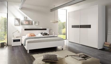 Dieses schicke Schlafzimmerset in weißem Hochglanz hat dunkle Highlights in Eichendekor und ein modernes Design - und wirkt dennoch sehr gemütlich.