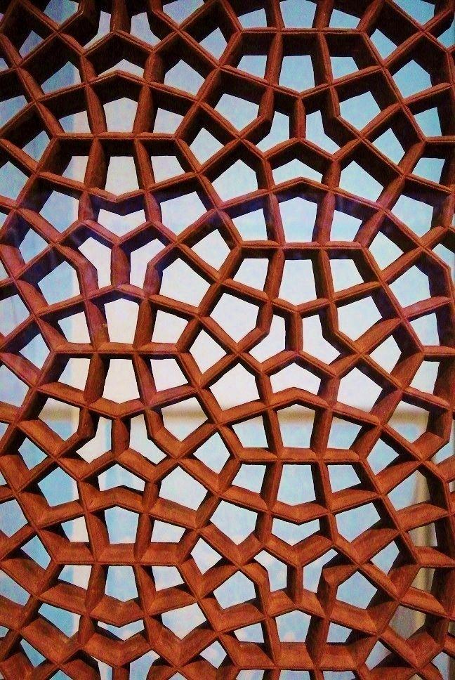 Jali-raamwerk, 19e eeuw. Dit open raamwerk, Jali genaamd, was bedoeld om in een venster te plaatsen en diende voor luchtcirculatie en als zonwering. Vrouwen konden door het raamwerk naar buiten kijken zonder zelf gezien te worden. Het abstracte patroon volgt een zeshoekraster. Gezien in het Tropenmuseum: Escher meets Islamic art.