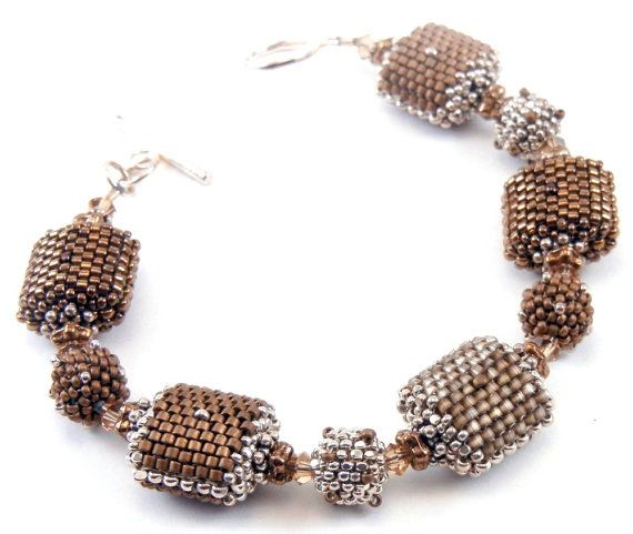 peyote stitch beaded beads in a glowing silk-satin taupe, rich matte brown, and shiny bronze. All are highlighted with sterling silver Czech charlottes. Accent beads are sterling silver, bronze and Swarovski crystals.