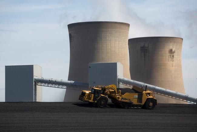 Bloomberg Vehicles Move Coal Ash As Cooling Towers Stand In The