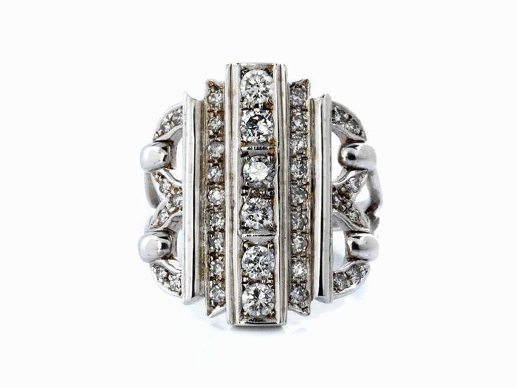 Ringweite: ca. 55. Gewicht: ca. 7,3 g. Ringkopflänge: ca. 2,1 cm. Breite: ca. 2 cm. WG 750. Breiter schöner Ring im Art déco-Stil besetzt mit Brillanten und...
