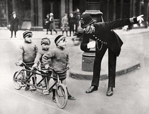 A police man gives three boys on a triple seater in London directions, early 20th century. So cute!