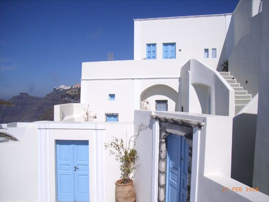 Traditional-Hotel-Exterior-Blue-Windows-Flowers-White-Fira-Santorini-Island