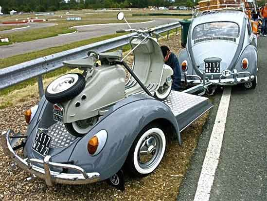 vw bug pulling a Lambretta scooter on a vw bug trailer. all shades of grey