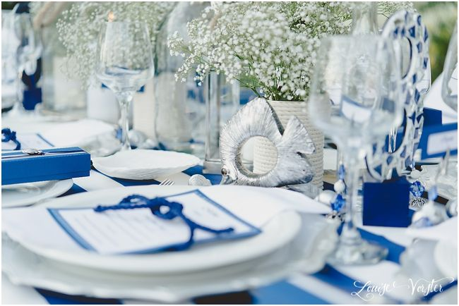 Blue and White table view. Baby's Breath Flowers in rope holder, fish details, menu on  white folded napkins with blue rope tie.