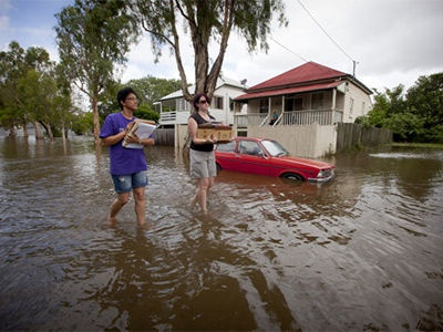 Residents of Newmarket, Brisbane walk through floodwaters as they carry photographs from their flooded Cullen street home on 28 Januarry, 2013.