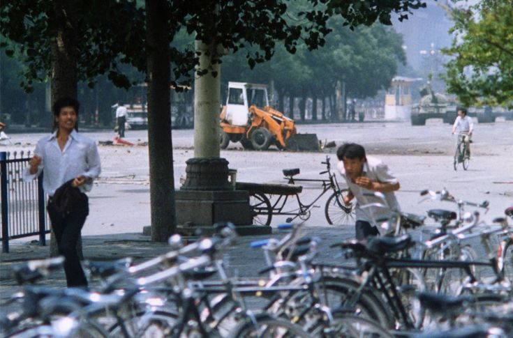 Another, recently unearthed photo of the Tank Man incident, which shows a new angle of his act of protest, now at a distance. Tank Man can be seen through the trees on the left, and the tanks can be seen on the far right.  (AP / Terril Jones)