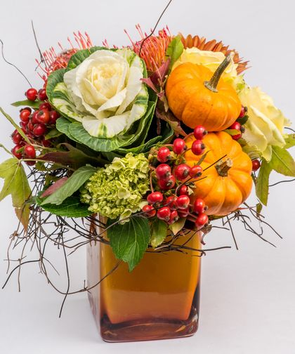 Pumpkin Spice - This unique and fun Fall arrangement is filled with all the colors and textures of the season. Designed in a copper-hued glass vase, this arrangement includes shades of oranges, whites, soft yellows and reds and is accented with mini pumpkins for a festive Fall feel.